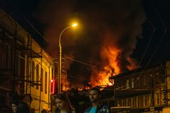 Rybinsk, Russia -31 July 2018 : Large night fire, burning modern building, smoke clouds, flames, people on street watching fire Stock Photos