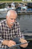 Rybołówstwo biznesmena mienia pastylka obrazy stock