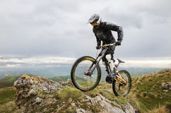 Ryder in full protective equipment on the mtb bike climbs on a rock against the backdrop of a mountain range and low Stock Image