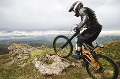 Ryder in full protective equipment on the mtb bike climbs on a rock against the backdrop of a mountain range and low Stock Photo