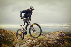 Ryder in full protective equipment on the mtb bike climbs on a rock against the backdrop of a mountain range and low Royalty Free Stock Photo