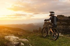 The rider in full protective equipment on the mtb bike is riding toward the sunset in the rays of the sunset sun against Stock Images