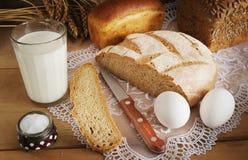 Rye bröd och ett exponeringsglas av mjölkar för matställe Arkivbild