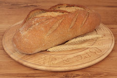 Rye Bread. Loaf with wheat on a carved rustic wooden board against oak wood background Royalty Free Stock Photos