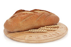 Rye Bread. Loaf on a wooden board with wheat sprigs, over white background Stock Photography