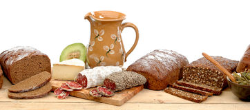 Rye bread with accessories on wood table. Still lifes with rye bread, sausages, cheese and olives on a wood table. In the background a fruit and a jug Stock Images