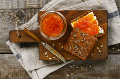 Rye bread and apricot jam sandwich on cutting board Stock Images