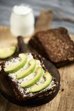 Rye bread with avocado, and yoghurt. Closeup of a slice of rye bread topped with some slices of avocado, and a glass jar of yoghurt, on a rustic wooden table Royalty Free Stock Photography