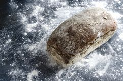 Whole loaf of yeast free bread on flour, dark surface.Concept of backed goods royalty free stock photography