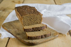 Rye bread on the board. And wooden table with white napkin Royalty Free Stock Images