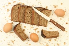 Rye bread and brown eggs. Sliced and crumbled rye bread with kitchen knife and three brown eggs on the white table with crumbles Stock Images