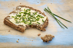 Rye bread with butter and chive. A slice of rye bread with butter and chive on painted cutting board stock photos