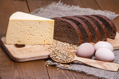 Rye bread and cheese on the background of sacking, wheat grains, eggs. Stock Photo
