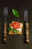 Rye bread with cheese, tomatoes and basil with a fork and knife Royalty Free Stock Image