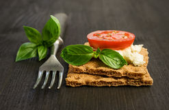 Rye bread with cheese, tomatoes and basil with a fork Stock Image