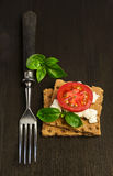 Rye bread with cheese, tomatoes and basil with a fork Royalty Free Stock Images