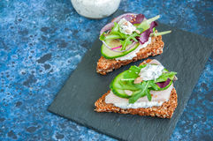 Rye bread crostini. Rye bread with seeds crostini with chicken ham  spring herbs red onion and spicy sour cream sauce served on a black stone board Stock Photos