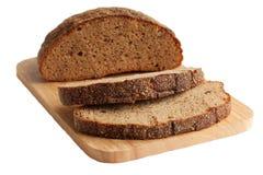 Rye bread on a cutting board. Half  of rye bread and slices on a cutting board. Isolated on white Royalty Free Stock Photo