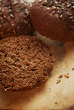 Rye Bread. Dark rye bread on an old and worn wooden cutting board with copy space. Shallow DOF Royalty Free Stock Photos