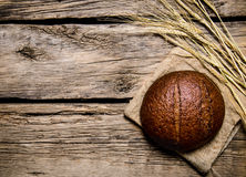 Rye bread with ears.  On wooden table. Royalty Free Stock Photography