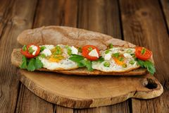 Rye bread egg bruscetta with tomatoes, cheese and greens Stock Photography