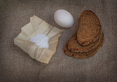 Rye bread, egg and salt on canvas Stock Photography