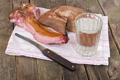 Rye bread, ham on edges and a glass of water Stock Photos