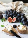 Rye bread and a knife with cream cheese and various fruits on a marble background. Cooking toast with cheese and berries. royalty free stock images