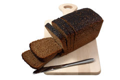 Rye bread and knife on a wooden board Royalty Free Stock Photos