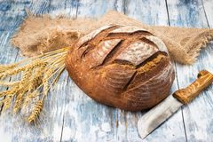 Rye bread lies on the burlap and a knife next to it. Stock Images