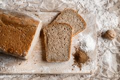 Rye bread on malt and flour, lies on the table. Near a pinch of flour and malt. Rye bread on malt and flour, lies on the table. A whole loaf and two cut pieces Royalty Free Stock Image