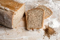 Rye bread on malt and flour, lies on the table. Near a pinch of flour and malt. Rye bread on malt and flour, lies on the table. A whole loaf and two cut pieces Royalty Free Stock Photos
