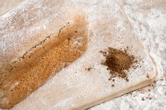 Rye bread on malt and flour, lies on the table. Near a pinch of flour and malt. Rye bread on malt and flour, lies on the table. A whole loaf and two cut pieces Stock Photography