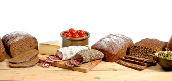 Rye bread on plank. Table with tomatoes,italian sausage, olives and cheese Royalty Free Stock Photos