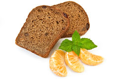 Rye bread with raisins and tangerines. Two slices of rye bread with raisins, three segment of mandarin, mint sprig with a light shade on white background Stock Image