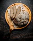 Rye bread on a round cutting Board. On dark rustic background royalty free stock image