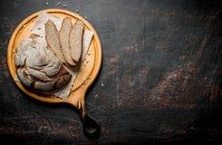 Rye bread on a round cutting Board. On dark rustic background stock photo
