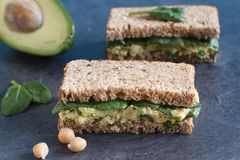 Rye bread sandwich with avocado, chickpeas and spinach. Healthy vegetarian sandwich with avocado, chickpeas and spinach Stock Photography