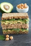 Rye bread sandwich with avocado, chickpeas and spinach. Healthy vegetarian sandwich with avocado, chickpeas and spinach Stock Photo