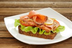 Rye bread sandwich with red fish, tomatoes and mustard Royalty Free Stock Image