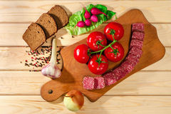 Rye bread, sausage, meat, cutting board, radish, tomatoes, onions, greens, garlic herb and spices on wooden background Royalty Free Stock Photography