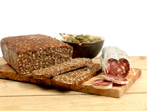 Rye bread and sausage. Rye bread in slices and Italian sausage and olives on a plank table.n Royalty Free Stock Images