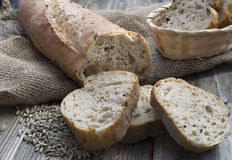 Rye bread with seeds. And a baskt full of slices of bread on wood background Stock Photos