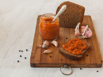 Rye bread slathered adjika on a cutting board Stock Photos