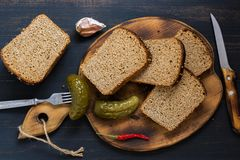 Rye bread is sliced with salted cucumber on a cutting board. Rye bread is sliced with salted cucumber on a cutting board Royalty Free Stock Image