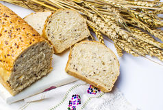 Rye bread slices with seeds and wheat plant. On a rustic tablecloth Royalty Free Stock Photos