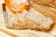Rye bread slices on wooden table. Cutted rye bread slices with seeds on a wooden board Royalty Free Stock Images