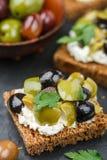 Rye bread toast canape with kalamata, black and green olives, feta chees. Rye bread toast canape with kalamata black and green olives, feta cheese and parsley stock photo