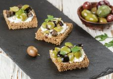 Rye bread toast canape with kalamata, black and green olives, feta chees. Rye bread toast canape with kalamata black and green olives, feta cheese and parsley stock image