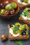 Rye bread toast canape with kalamata, black and green olives, feta chees. Rye bread toast canape with kalamata black and green olives, feta cheese and parsley royalty free stock images